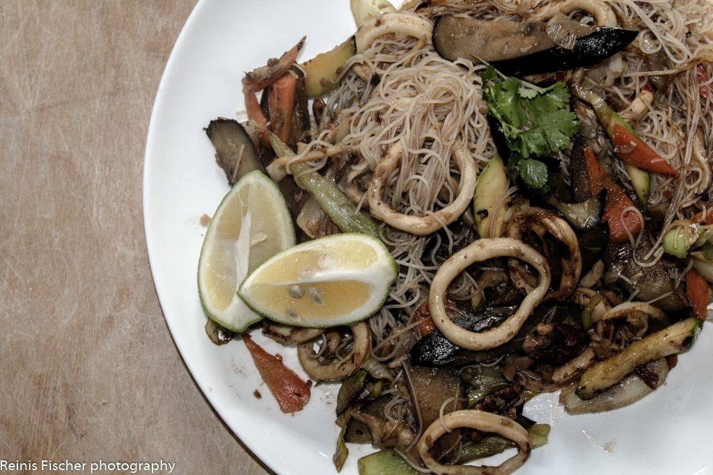 Asian Cuisine - Rice noodles, fried vegetables and a squid