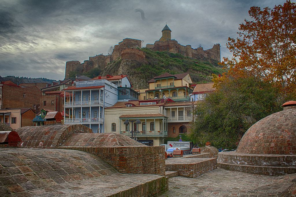 Public bath houses, colorful balconies and Narikala fortress on top