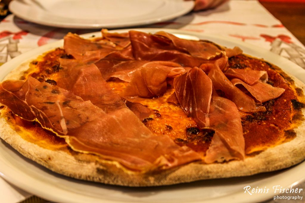 Four formage pizza topped with a lot of prosciutto