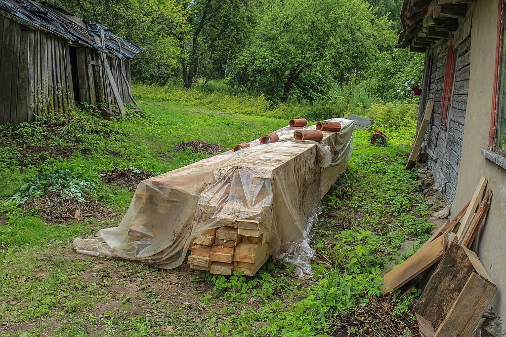 Beams and laths covered with sheet to protect against rain